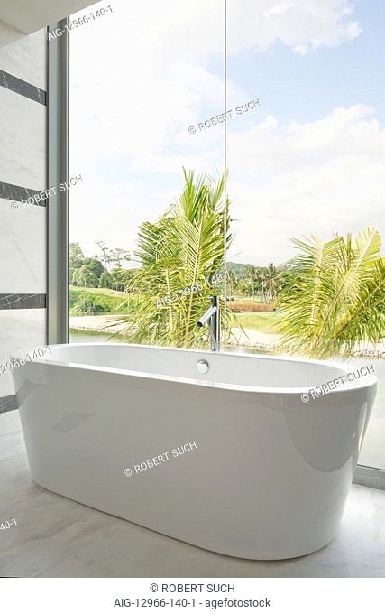 Modern ceramic bathtub and glass picture windows with view