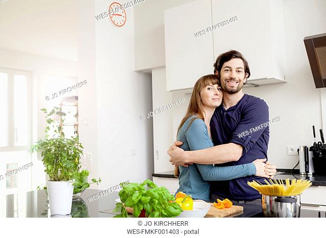 Happy couple embracing in kitchen