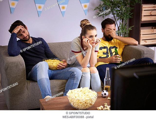 Disappointed friends sitting on the sofa watching Tv