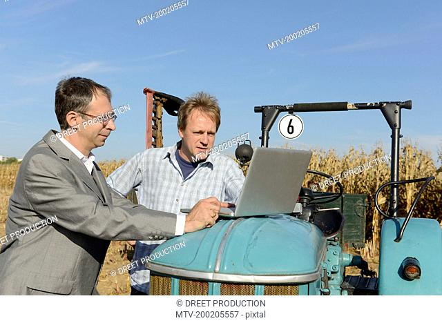 Farmer and businessman checking dates in laptop on cornfield, Bavaria