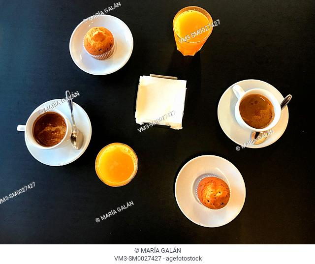 Breakfast: two cups of coffee, two orange juices and two muffins. View from above