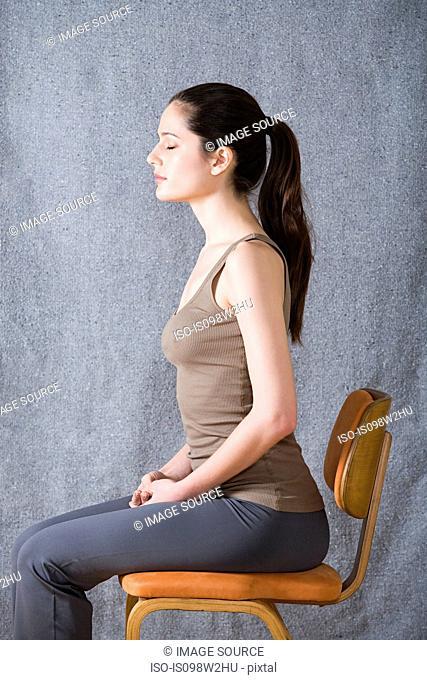 Women sitting on chair, eyes closed