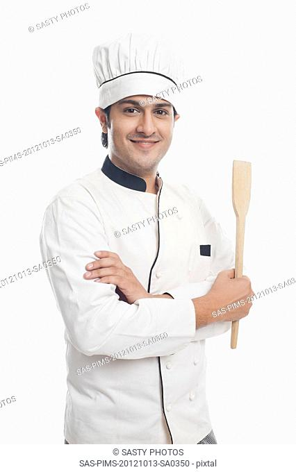 Portrait of a male chef holding a spatula and smiling