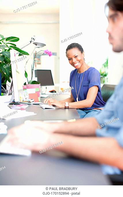 Portrait of smiling businesswoman at desk in office