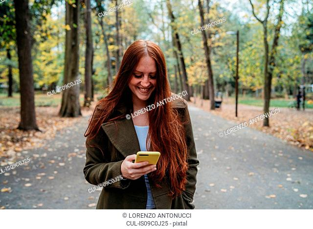 Young woman with long red hair looking at smartphone in tree lined autumn park, Florence, Tuscany, Italy
