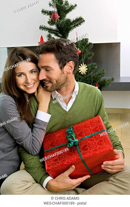 Happy couple with Christmas present at home