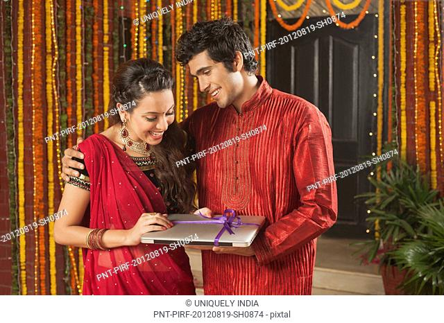 Man giving a laptop to his girlfriend on Diwali