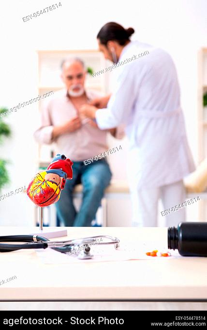 Old man visiting young doctor cardiologist