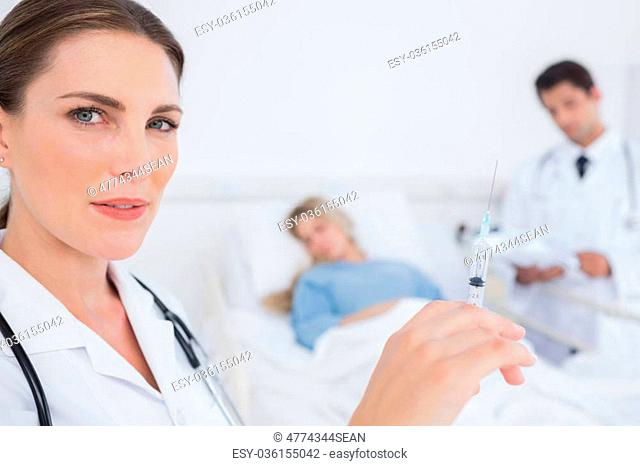Serious doctor with a syringe in front of a patient and a doctor