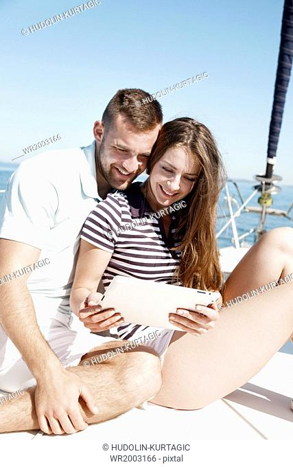 Young couple using digital tablet on sailboat, Adriatic Sea