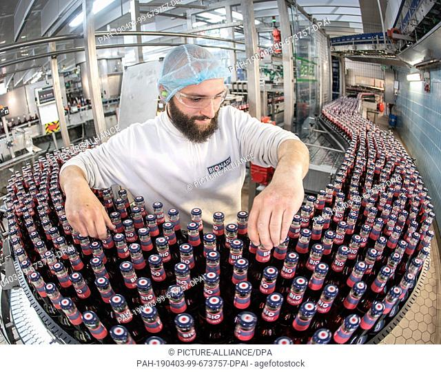 03 April 2019, Bavaria, Ostheim Vor Der Rhön: During the bottling process at the Lower Franconian production site, one employee stands on a conveyor belt with...