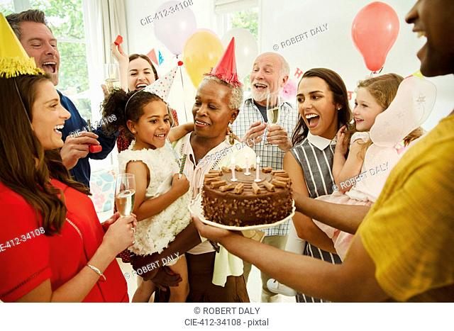 Multi-generation family celebrating birthday with chocolate cake