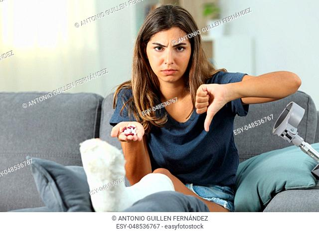 Angry disabled woman holding pills with thumbs down sitting on a couch in the living room at home