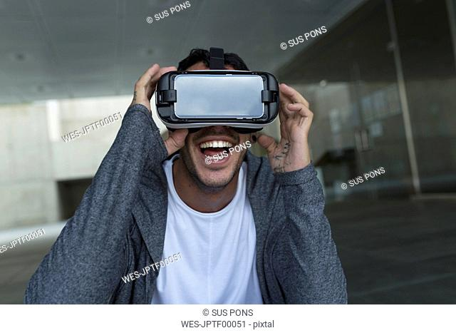 Excited young man wearing Virtual Reality Glasses