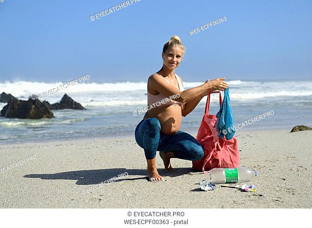 Pregnant woman cleaning the beach from plastic waste