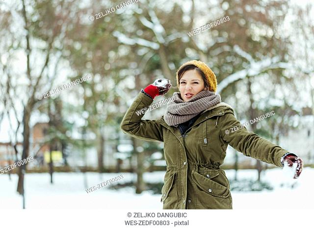 Portrait of woman throwing snowball