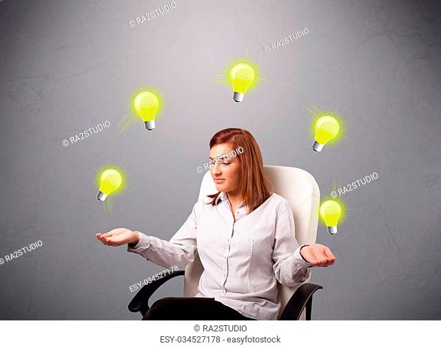 beautiful young lady sitting and juggling with light bulbs