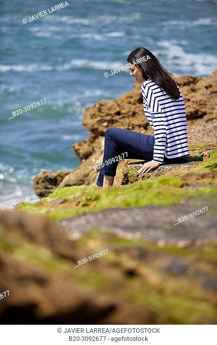 Woman in sailor clothes, Costa rocks, Plage du Port Vieux, Biarritz, Pyrenees Atlantiques, France, Europe