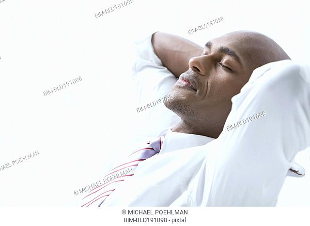 Mixed race businessman with hands behind head and eyes closed