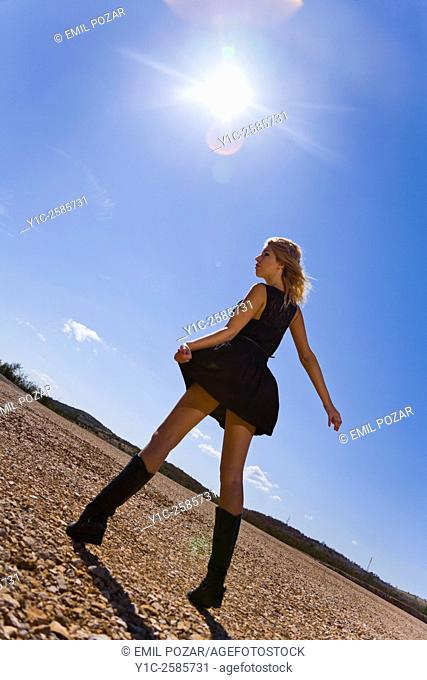 Young woman against glaring sun