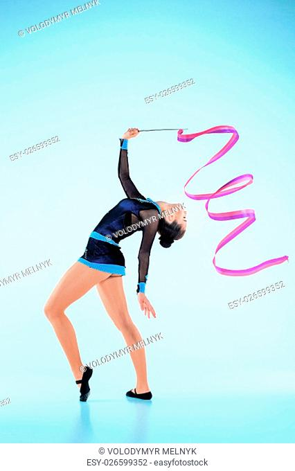The girl doing gymnastics dance with colored ribbon on a gray background