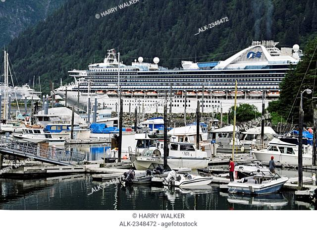 Princess Cruises ship Star Princess moored at Broadway Dock in Skagway Alaska; Small Boat Harbor in foreground with 2 people fishing off floating dock; another...