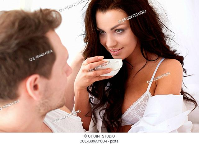 Sexy young woman drinking coffee in bed with boyfriend