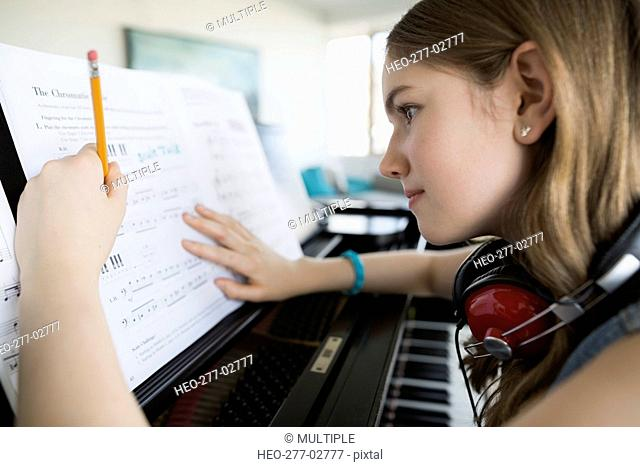Girl with headphones writing music at piano