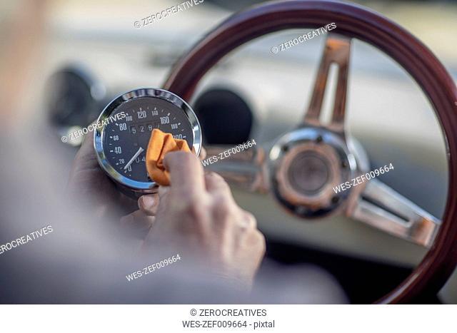 Senior man polishing tachometer of a car