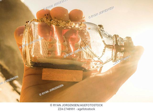 Seaside take on a hand capturing a little model ship in a clear glass bottle with sunlight beaming in from corner