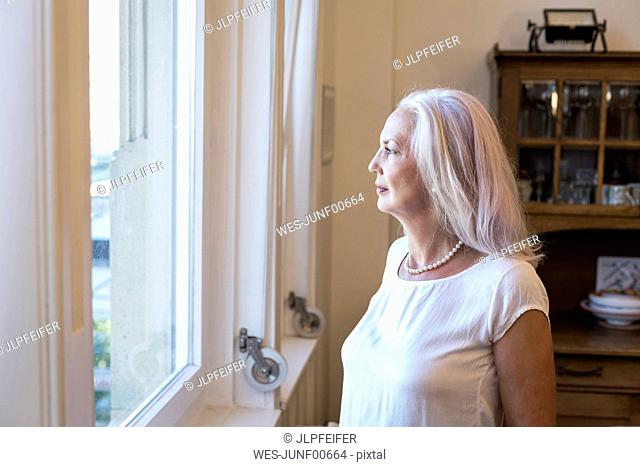 Mature woman looking through window at home