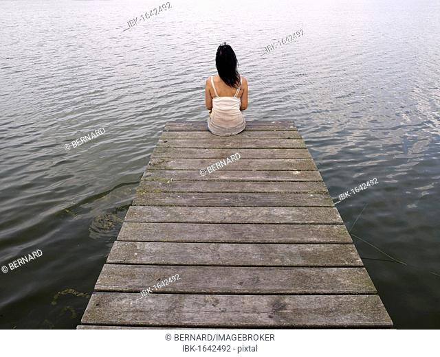 Woman sitting on a wooden pier at a lake, Mecklenburg Lake District, Mecklenburg-Western Pomerania, Germany, Europe
