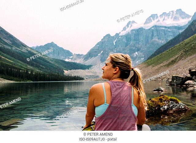 Rear view of mid adult woman sitting at waters edge looking away, Moraine Lake, Banff National Park, Alberta Canada