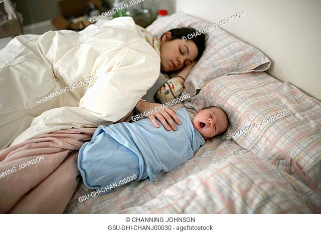 Mother and Newborn Baby Sleeping in Bed
