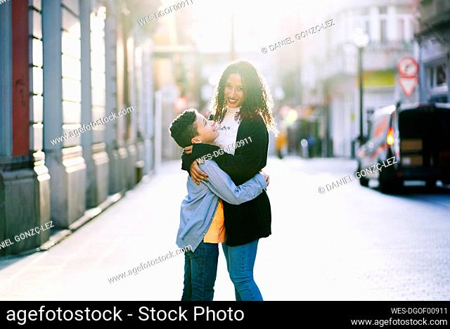 Mother and son hugging each other in the city