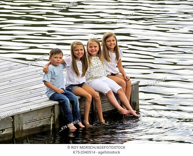 Four children sitting on a dock with their feet in the water