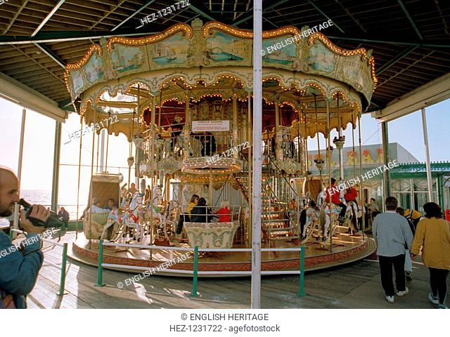 Venetian Carousel, North Pier, Blackpool, Lancashire, 1999. Children ride around on this unusual two storey carousel. In the background is the sea while on the...
