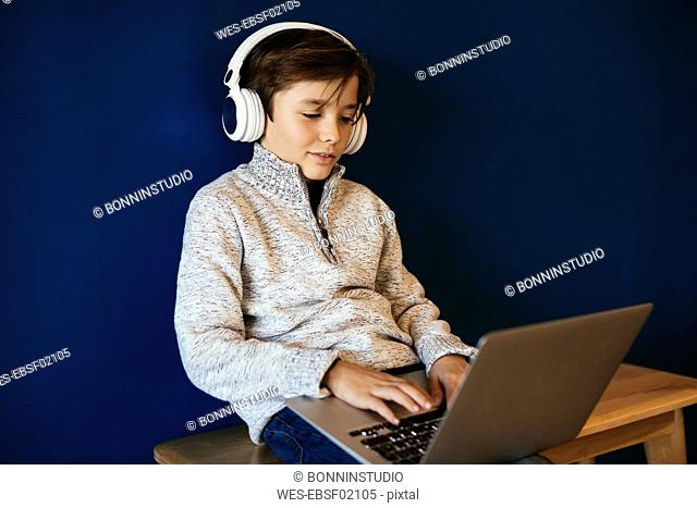 Boy sitting on bench wearing headphones and using laptop