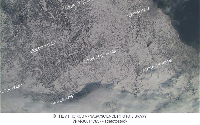 Snowy landscape seen passing 200 miles below the International Space Station. The feathery outlines of drainage patterns running off the landscape can be seen...