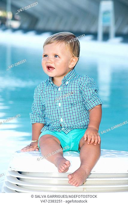 Picture a baby sitting beside a pool