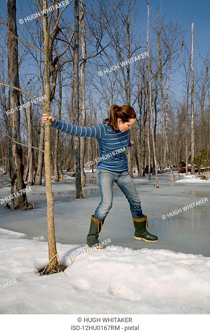 Woman Testing Ice on Pond