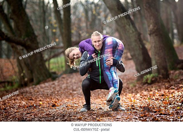 Mid adult man crouching in forest carrying young woman on shoulders looking at camera smiling