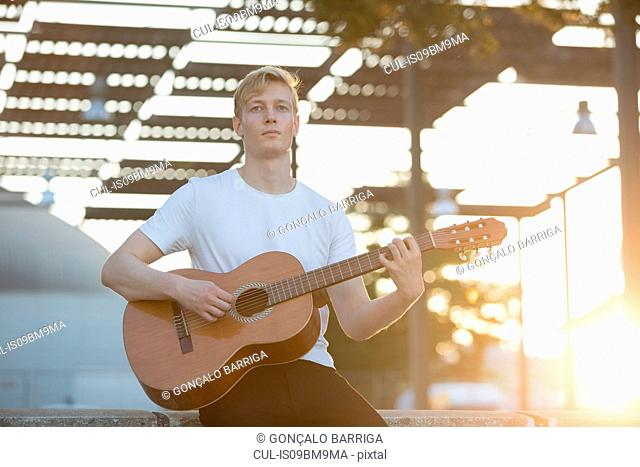 Young musician playing guitar in park