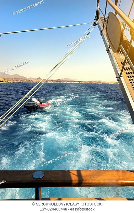Wooden sailboat tows rubber boat in the sea