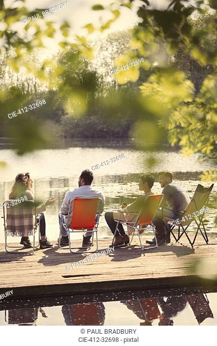 Friends talking at sunny lakeside dock