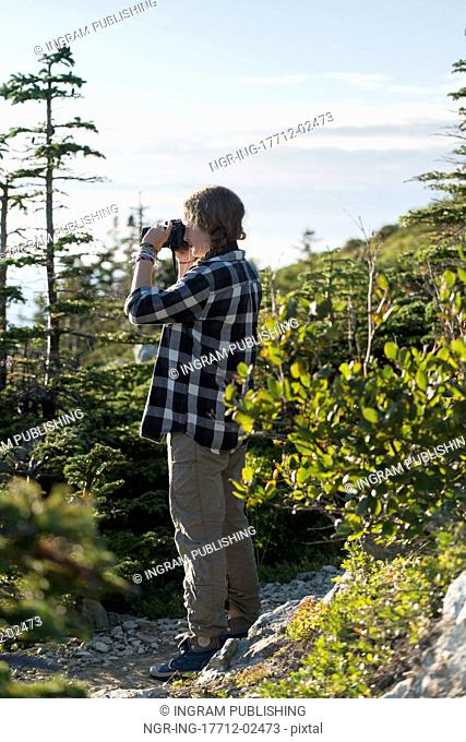 Girl taking pictures on Long Point Hiking Trail, Crow Head, North Twillingate Island, Newfoundland And Labrador, Canada