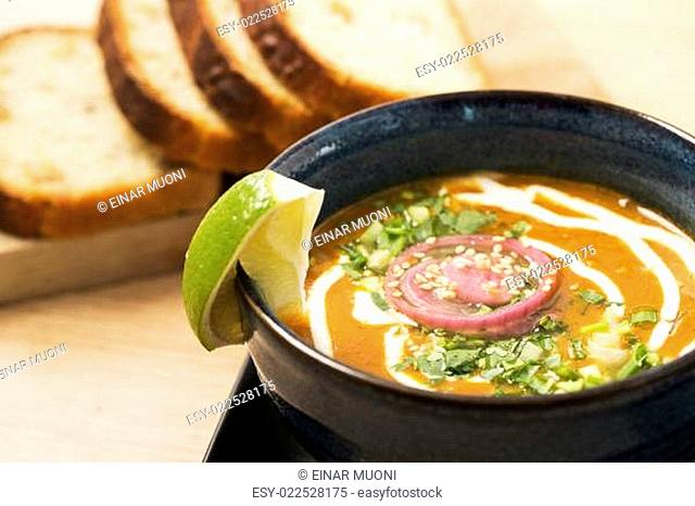 Bowl with reflective soup with juicy lemon