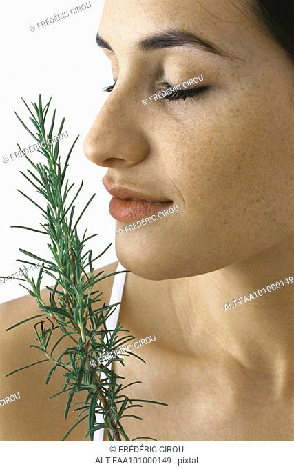 Young woman smelling spring of fresh rosemary, eyes closed