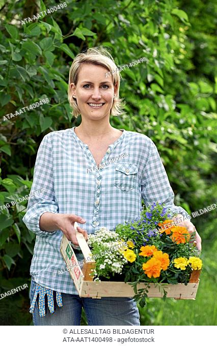 Woman in the garden with a basket full of plants