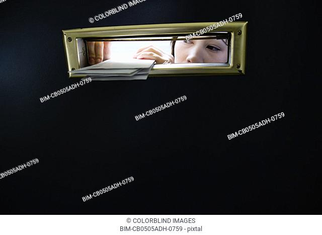 Woman putting letters through mail slot